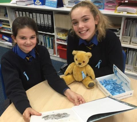 A picture of Georgia and Katie at school with their teddy, books and blue dyslexia awareness ribbons.
